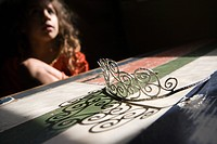 Girl looking at tiara on table (thumbnail)