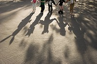 Five children in fancy dress holding hands, casting shadow