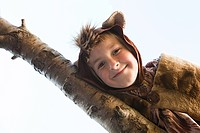 Boy dressed up as bear on tree branch