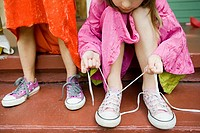 Two girls, one tying up shoelace