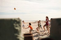 Boys playing football on beach, view through wall
