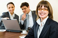 Smart woman in glasses smiles on a background of her the coworkers in the office