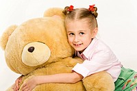 Portrait of cute little girl embracing her teddy bear and smiling