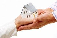 Close_up of female hands passing toy model of house to male