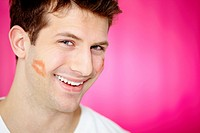 Handsome man with print of lipstick on his cheek smiling at camera