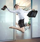 Woman jumping in air, legs tucked under                                                                                                               ...