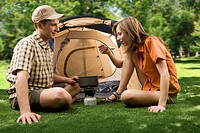 Photo of cheerful girl holding cup while her boyfriend pouring tea into it in the park