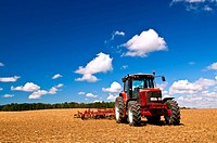 Small scale farming with tractor and plough in field