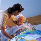 A geriatric nurse caring for a senior citizen lying in bed