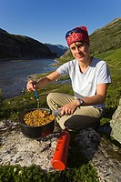 Young woman preparing a meal, cooking outdoors, MSR fuel stove, Happy Camp, historic Chilkoot Pass, Chilkoot Trail, Long Lake behind, Yukon Territory,...