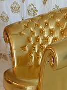 Details of a luxurious, gold_colored chair in the Chesterfield_style in a sophisticated atmosphere