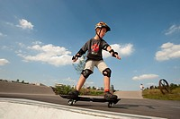 Boy, 11 years, with waveboard and protective gear in a fun park