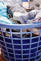 Plastic laundry basket full of clothing