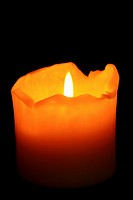 A burning, well used candle with ragged melting edges against a dark background  Isolated