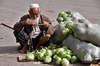 Old man weighing cauliflowers in a market  Kashgar, Xinjiang, China