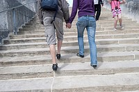 Young couple going up the stairs together, hand in hand, from behind
