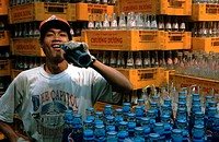 Soft drinks, young man wearing a Coca-Cola hat, pepsi and coke bottles in beverage crates of a Vietnamese brand, Vietnam, Asia