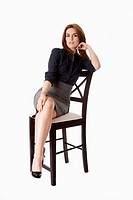 Beautiful brunette business woman sitting wearing gray skirt and blue blouse with hand on leg with legs crossed, isolated