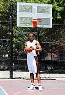 Handsome sporty African-American male basketball player with attitude dressed in white standing holding his ball with both hands outdoor on a summer d...