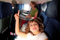 little girl inside aircraft rising up finger smiling