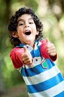 Little Latin_American boy playing outdoors with thumbs up.