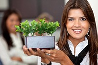 Beautiful business woman with a green plant