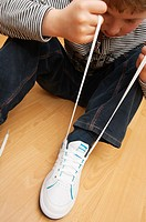 A picture of a seven year old boy learning to tie his shoelaces in the Uk