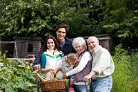 A family standing on an allotment, holding a basket full of vegetables
