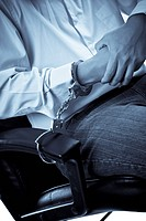 A conceptual shot of a businessman being handcuffed to an office chair