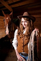 A portrait of a happy beautiful caucasian cowgirl with a horse