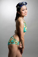 A shot of a beautiful asian woman in swimsuit wearing snorkelling goggles