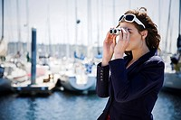 A beautiful caucasian woman at the marina looking through binoculars