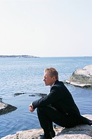 Young businessman sitting on coastline and looking at view