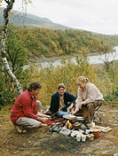 Three people sitting next to campfire during fishing trip
