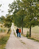 Mature couple walking along country road