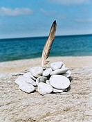 Bird´s feather and pebble stack with sea in the background