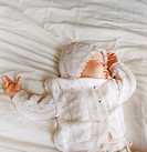 Baby girls dressed in white baby clothes sleeping in bed