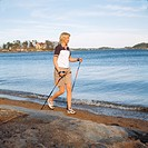 Mature woman nordic walking on water´s edge