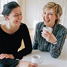 Pair of cheerful mature women over cup of tea