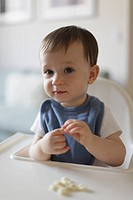 Baby in high chair eating a snack.