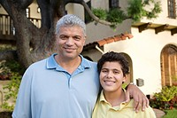 Hispanic father and son in front of house