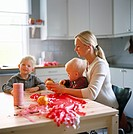 Woman with two sons doing Christmas decorations in kitchen