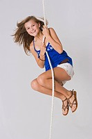 Teenage girl hanging from a rope