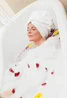 Pretty woman taking a relaxing bath with a towel on her head
