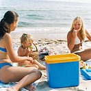 Women with girl having picnic on beach