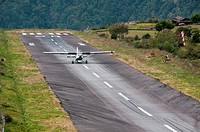 small plane landing on the dangerous and tiny Lukla airstrip in the Everest Region of Nepal