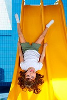 Brunette little girl upside down playground slide modern city buildings