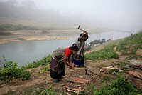Tribal women chopping wood nearby Sangu river at Thanchi Bandarban, Bangladesh December 2009