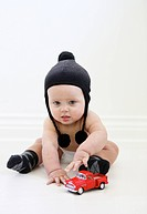 Baby boy in diaper and winter hat playing with a truck