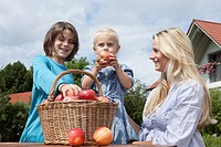 Germany, Munich, Mother with children eating apples from basket